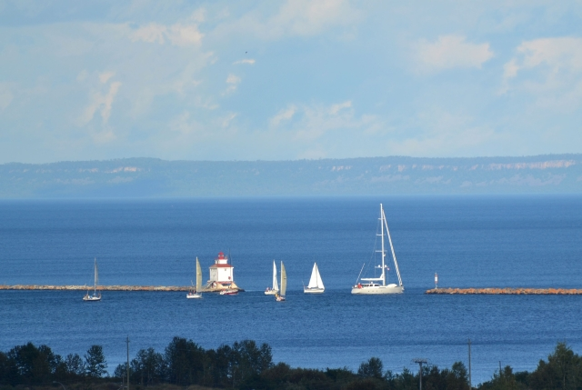 SAILBOATS JOSTLE THROUGH BREAKWATER OPENING