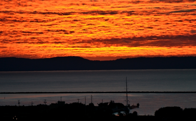 FIERY SUNRISE CLOUDS OVER MOORED SAILBOAT
